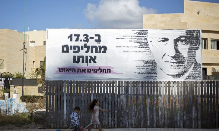 Children pass by an election campaign banner with a painting of Israel's Prime Minister Benjamin Netanyahu, in Netanya, Israel, Monday, March 2, 2015. (AP Photo/Ariel Schalit)