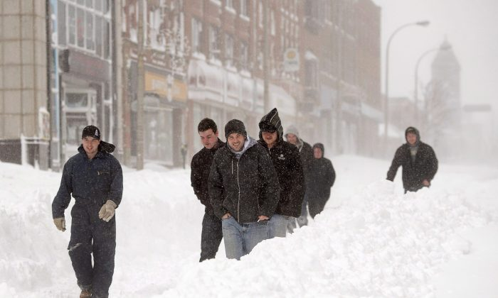 Pedestrians brave the elements in downtown Charlottetown on Feb. 16, 2015. The Weather Network says the bitter cold and record snowfalls that have made this a tough winter across most of the country means spring weather will be a while in coming—the only exception being B.C. (The Canadian Press/Andrew Vaughan)