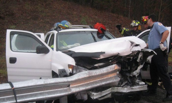 Firefighters and rescue personnel attend the scene of a car accident in Bristol, Tenn., on Dec. 17, 2008. Authorities across Canada are awaiting test results from the U.S. before deciding what to do about thousands of safety devices with alleged defects that could cause guardrails to rip through cars and motorists instead of protecting them in crashes. (The Canadian Press/Joshua Harmon)