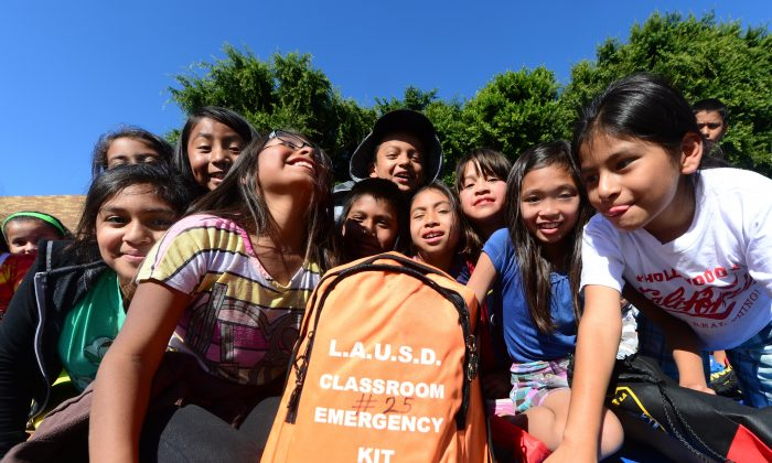 Fourth-grade schoolchildren crowd around an emergency kit backpack which each class has during an earthquake drill at Rosemont Elementary School in Los Angeles on October 17, 2013. (Frederic J. Brown/AFP/Getty Images)