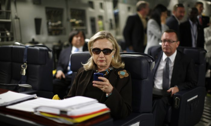 Then-Secretary of State Hillary Rodham Clinton checks her Blackberry from a desk inside a C-17 military plane upon her departure from Malta on Oct. 18, 2011. (Kevin Lamarque/AP Photo)