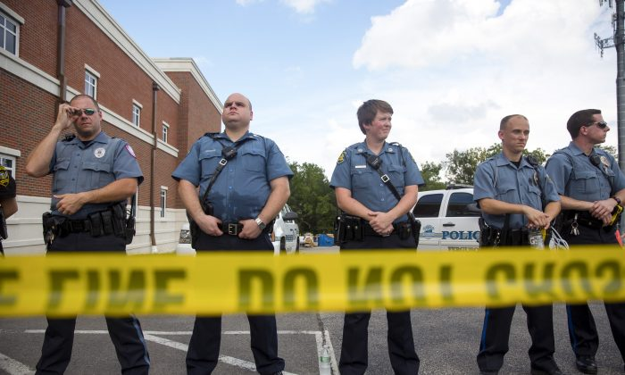 Ferguson police officers stand guard during a rally for Michael Brown outside their headquarters in Ferguson, Mo., on Aug. 30, 2014. ( Aaron P. Bernstein/Getty Images)