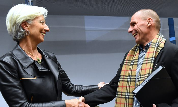 Greek Finance Minister Yanis Varoufakis (R) shakes hands with International Monetary Fund (IMF) Director Christine Lagarde during an emergency Eurogroup finance ministers meeting at the European Council in Brussels on Feb. 11, 2015. (Emmanuel Dunand/AFP/Getty Images)