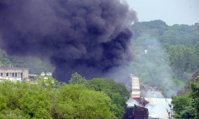 Smoke rises from a derailed train in White Marsh, Md., on May 28, 2013. The cargo train crashed into a garbage truck near Baltimore and exploded after it derailed. (Steve Ruark/Getty Images)