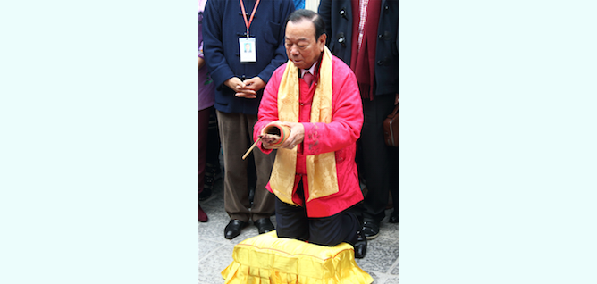 Lau Wong-fat, chairman of the Heung Yee Kuk (Rural Council), shakes a bamboo container with fortune sticks on the second day of Chinese New Year. (Poon/Epoch Times