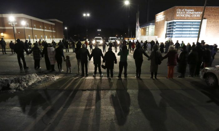 Protestors block traffic outside the Ferguson Police Department, Wednesday, March 4, 2015, in Ferguson, Mo., after the Department of Justice released a report documenting abuses within the police department. (AP Photo/Charles Rex Arbogast)