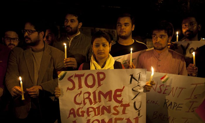 Indian youth hold candles during a protest against sexual violence in New Delhi on Feb. 9, 2015. (AP Photo/ Tsering Topgyal)