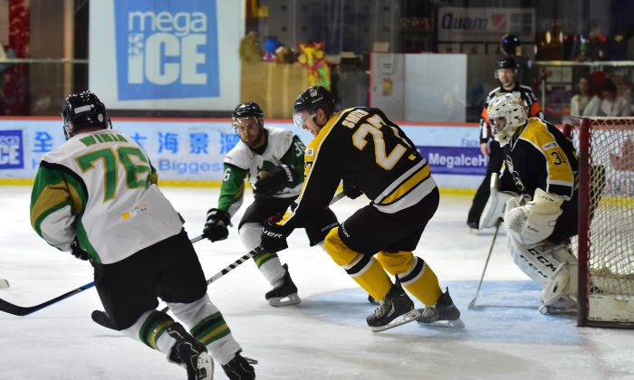 Hong Kong Tycoons' Brad Smith back defending against an attack by Macau Aces in their 2nd best-of-three CIHL semi-final at Mega Ice on Saturday Feb 28. Tycoons edged a tight match 3-2 with an overtime goal to move into the Final to be played on March 14, 2015. (Bill Cox/Epoch Times)