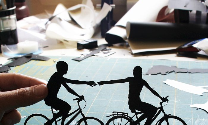 "Joe Bagley 's ""Holding Couple Riding Bikes"" as sold on Etsy. Bagley, of Boston, painstakingly hand-cuts intricate paper art.  (AP Photo/Joe Bagley)"