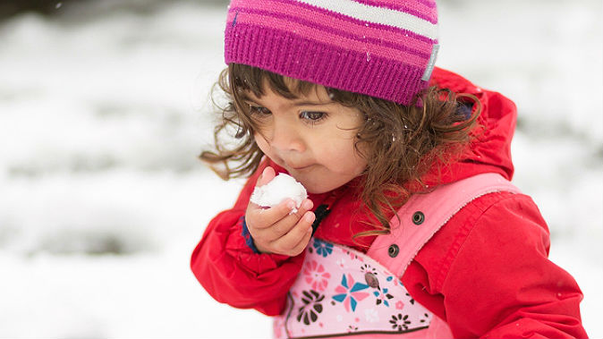 Girl is about to eat snow. (Shutterstock*)