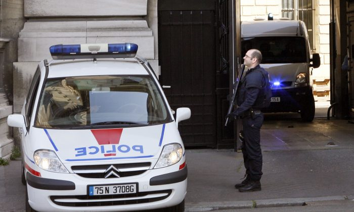 A police officer stands guard in front of the Paris justice court as a detenee's convoy drives out on April 27, 2010. (Thomas Samson/AFP/Getty Images)