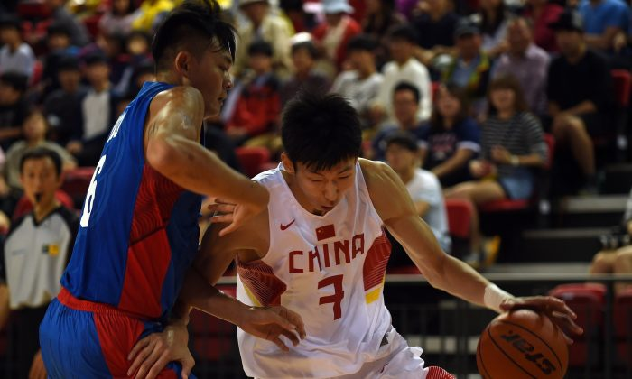 China's Zhou Qi dribbles past Taiwan's Wu Tai Hao during their men's basketball match at the 2014 Asian Games at the Samsan World Gymnasium in Incheon on September 25, 2014. (AFP/Getty Images)