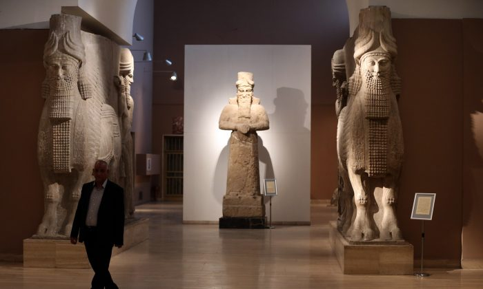 "In this March 1, 2015. file  photo, a man at Iraq's National Museum in Baghdad walks past two ancient Assyrian human-headed winged bull statues. Islamic State militants ""bulldozed"" the renowned archaeological site of the ancient city of Nimrud in northern Iraq on Thursday, March 5, 2015, using heavy military vehicles, the government said. Nimrud was the second capital of Assyria, an ancient kingdom that began in about 900 B.C., partially in present-day Iraq, and became a great regional power. The city, which was destroyed in 612 B.C., is located on the Tigris River just south of Iraq's second largest city, Mosul, which was captured by the Islamic State group in June(AP Photo/Karim Kadim, File)"