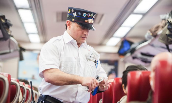 Metro North train conductor Steve Macchio, inspects tickets on the 4 p.m. train from Grand Central Terminal in New York City to New Haven on March 27, 2015. (Petr Svab/Epoch Times)