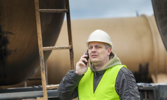 Railroad employee with cell phone near tank wagon. (Shutterstock*)