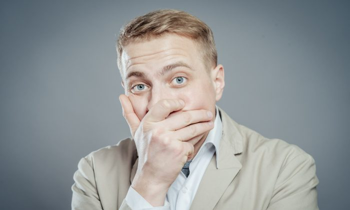 Businessman covers mouth with hand. (Shutterstock*)