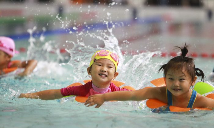 A group of young Chinese children swim in Beijing on Sept. 22, 2012. Chinese Premier Li Keqiang indicated on March 5 that China may reform its controversial one-child policy. (STR/AFP/Getty Images)