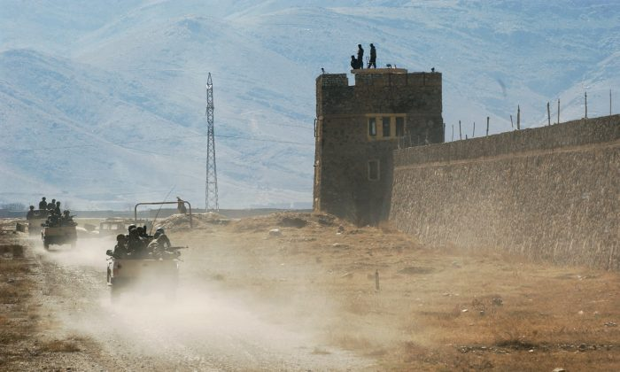 A convoy of Afghan National Army drive around the Poldicharki Prison in Kabul, Afghanistan on Sunday, Feb. 26, 2006. (AP Photo/Musadeq Sadeq)