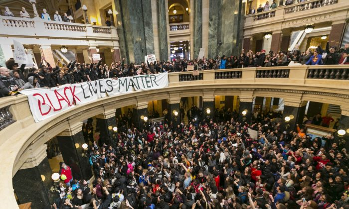 Demonstrators protest the shooting of Tony T. Robinson, at the state Capitol Monday, March 9, 2015, in Madison, Wis. Robinson, 19, was fatally shot Friday night by a police officer who forced his way into an apartment after hearing a disturbance. Police say Robinson had attacked the officer. (AP Photo/Andy Manis)