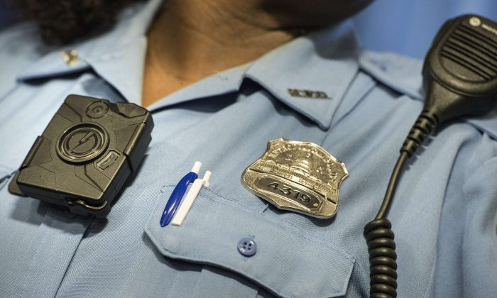 Washington DC Police Officer Debra Domino models a body camera before a press conference at City Hall Sept. 24, 2014 in Washington, DC. (Brendan Smialowski/AFP/Getty Images)
