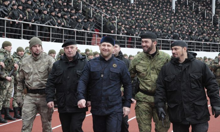 """In this file photo taken on Sunday, Dec. 28, 2014, Chechnya's regional leader Ramzan Kadyrov, center, and other Chechen top commanders inspect Chechen special forces during a a rally at the Dinamo stadium in Chechen capital Grozny, Russia. Russian President Vladimir Putin bestowed a state award Monday on the leader of Chechnya, the North Caucasus strongman who hailed the suspected killer of an opposition politician as a """"true patriot.""""Kadyrov drew criticism Sunday from government opponents after praising Zaur Dadayev, a Chechen suspect in the murder of Kremlin foe Boris Nemtsov. (AP Photo/Musa Sadulayev, file)"""
