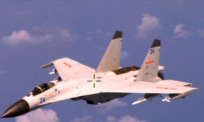 An armed Chinese J-11 fighter jet, a 1992 copy of the Russian Su-27, flies near an American patrol aircraft over the South China Sea in international airspace on Aug. 19, 2014. (U.S. Navy Photo/Released)