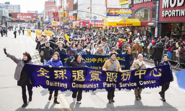 Falun Gong practitioners carry a banner asking people to quite the Chinese Communist Party during a parade in Flushing in 2014. (Dai Bing/Epoch Times)