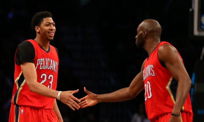 New Orleans Pelicans' forward Anthony Davis (23) celebrates with teammate Quincy Pondexter (20) during the second half of an NBA basketball game against the Brooklyn Nets, Tuesday, March 10, 2015, in New York. New Orleans won 111-91. (AP Photo/Adam Hunger)