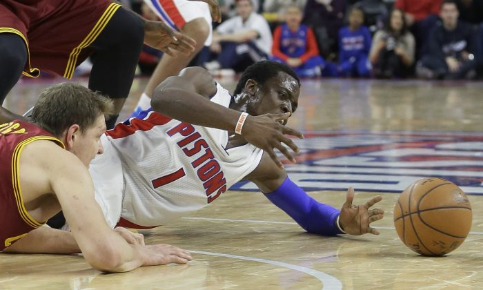 Detroit Pistons guard Reggie Jackson (1) and Cleveland Cavaliers center Timofey Mozgov of Russia chase a loose ball during the second half of an NBA basketball game, Tuesday, Feb. 24, 2015 in Auburn Hills, Mich. (AP Photo/Carlos Osorio)