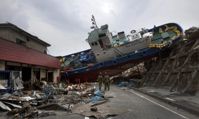 Two Japanese soldiers stop to look at a ship blocking a road in the tsunami destroyed town of Onagawa, Miyagi Prefecture, northeastern Japan. Japan marks four years since the earthquake, tsunami, and nuclear disaster on Wednesday, March 11. (AP/David Guttenfelder)