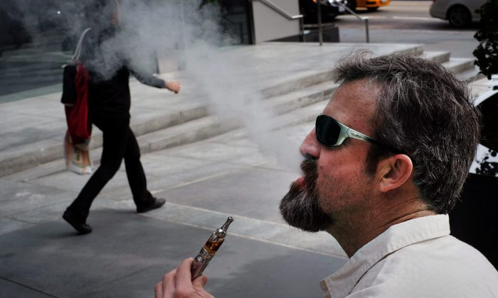 A man smokes an electronic cigarette in the street. (AP Photo/Richard Vogel)