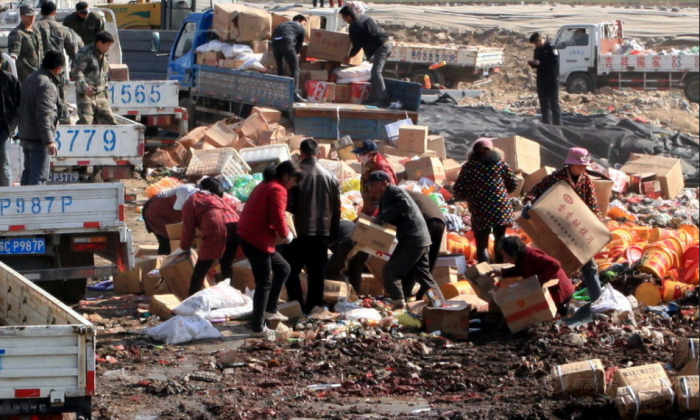 A photograph on Sina News, a Chinese website, shows people in the city of Xuzhou, Jiangsu Province, scrambling to salvage the boxes of substandard and counterfeit foodstuffs being destroyed and discarded by local authorities on March 11. Some came back for several helpings. (Screenshot/Epoch Times)