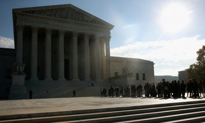People stand in line to enter the US Supreme Court building, November 12, 2014, in Washington, DC. (Photo by Mark Wilson/Getty Images)
