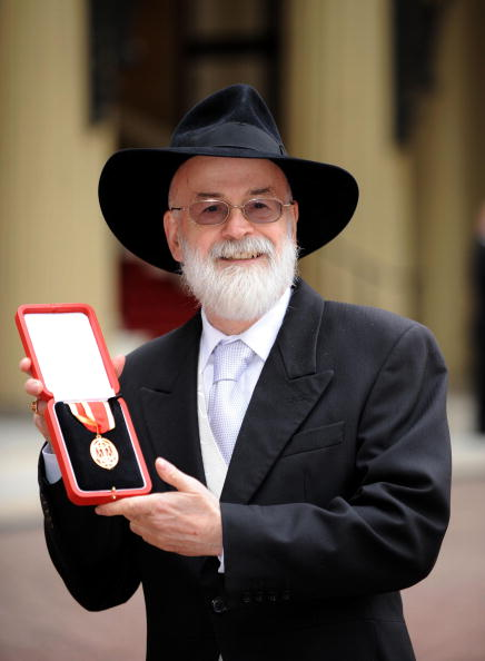 Sir Terry Pratchett poses for photographs after he was knighted by Queen Elizabeth II at Buckingham Palace on February 18, 2009 in London, England.  (Photo by Ian Nicholson - WPA Pool/Getty Images)