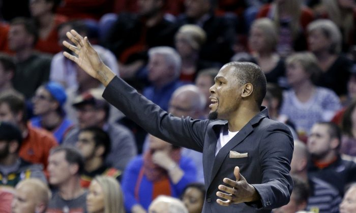 Oklahoma City Thunder forward Kevin Durant, who did not play, reacts from the bench during the second half of an NBA basketball game against the Portland Trail Blazers in Portland, Ore., Friday, Feb. 27, 2015. Portland beat Oklahoma City 115-112. (AP Photo/Don Ryan)