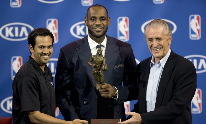 In this May 5, 2013 photo, Miami Heat NBA basketball player LeBron James, center, poses with Heat coach Erik Spoelstra, left, and team president Pat Riley after winning the NBA Most Valuable Player award, in Miami. (AP Photo/J Pat Carter)