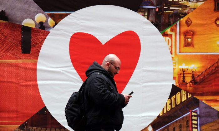 A man texts on his smartphone as he walks along a street in New York on March 4, 2015. Social dating app Tinder announced it will limit right swipes, in effort to emulate real life relationships. (Jewel  Samad/AFP/Getty Images)