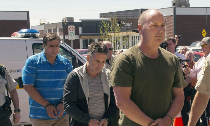 Former Montreal Maine and Atlantic Railway Ltd. employees Tom Harding (R), Jean Demaitre (C) and Richard Labrie are escorted by police to appear in court in Lac-Megantic on May 13, 2014. Harding is now back in court to have a date set for a preliminary hearing—something his lawyer says prosecutors are seeking to prevent. (The Canadian Press/Ryan Remiorz)