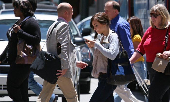 A woman text messages while walking across the street in San Francisco in June 29, 2010.  (AP Photo/Ben Margot)