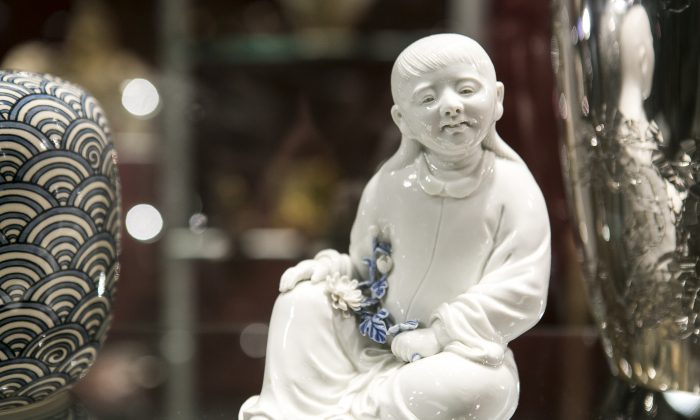A Hirado porcelain okimono of a seated Kikujido, the beloved chrysanthemum boy from the late Edo period, Japan, at the Flying Cranes Antiques booth during the Asia Art Fair at the Bohemian National Hall in New York City, on March 12, 2015. (Samira Bouaou/Epoch Times)