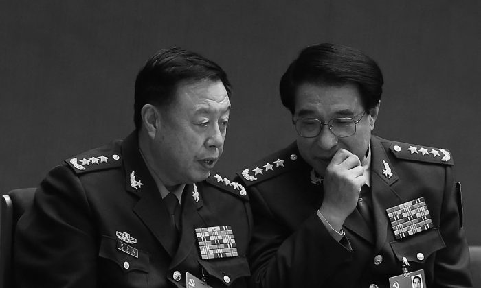 Chinese vice chairmen of the Central Military Commission Xu Caihou (R) and Fan Changlong talk during the closing session of the 18th National Congress of the Communist Party of China at the Great Hall of the People on Nov. 14, 2012 in Beijing, China. Xu, under investigation for bribery, died from cancer on March 16, according to state news media. (Lintao Zhang/Getty Images)
