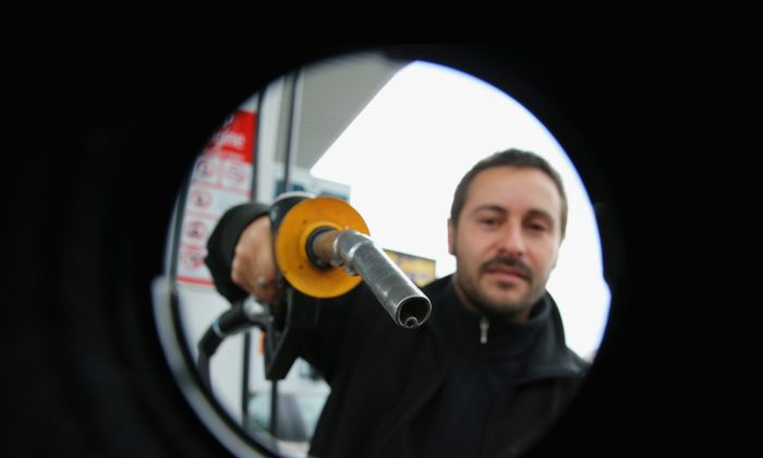 Man uses a fuel dispenser to fill his car up with petrol at a petrol station on July 23, 2013. (Scott Barbour/Getty Images)