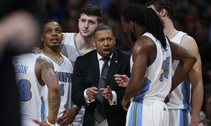 Denver Nuggets interim head coach Melvin Hunt, center, confers with his players during a time out against the Golden State Warriors in the fourth quarter of an NBA basketball game Friday, March 13, 2015, in Denver. The Nuggets won 114-103. (AP Photo/David Zalubowski)