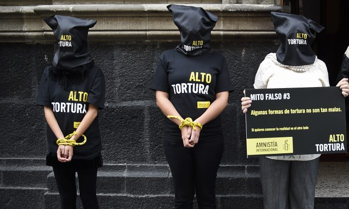 "Activists of Amnesty International demonstrate against torture in Mexico, before submitting to the press a report titled ""Out of control: Torture and other ill-treatment in Mexico"" in Mexico City on Sept. 4, 2014. (Ronaldo Schemidt/AFP/Getty Images)"
