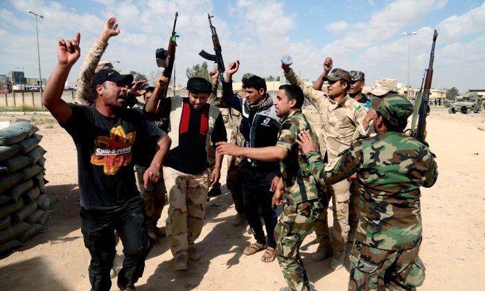 Iraqi fighters chant slogans against extremists at the front line during a battle against ISIS militants in Tikrit, Iraq, on March 16, 2015. (AP Photo/Khalid Mohammed)