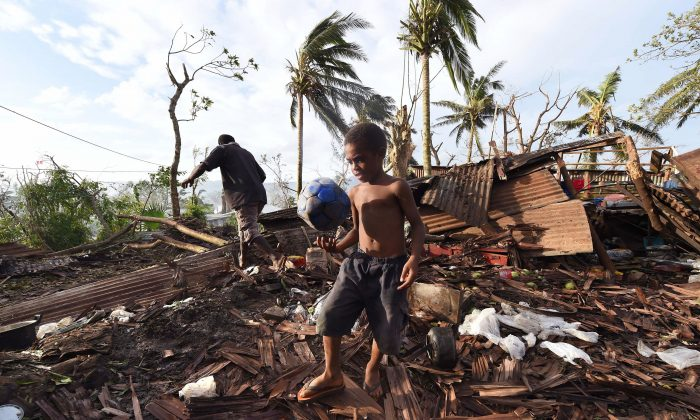 Samuel, only his first name given, carries a ball through the ruins of their family home as his father, Phillip, at back, picks through the debris in Port Vila, Vanuatu in the aftermath of Cyclone Pam, March 16, 2015. (AP Photo/Dave Hunt)