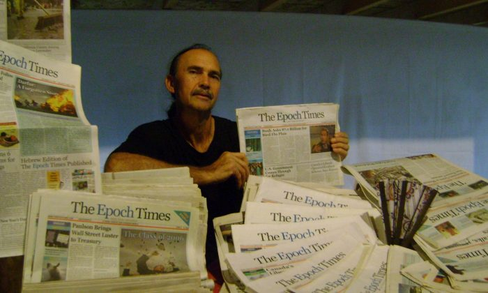 Steven Hersom shows his collection of past issues of the Epoch Times. After reading the Epoch Times, Mr. Hersom was moved to start distributing the paper on his own so that more people could read it. (Sophia Fang/Epoch Times)