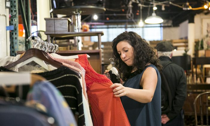 A woman looks through vintage clothes at Film Biz Recycling, a shop that sells donated items from movie and theater sets, in the Gowanus area of Brooklyn, New York, on Oct. 30, 2014. (Samira Bouaou/Epoch Times)