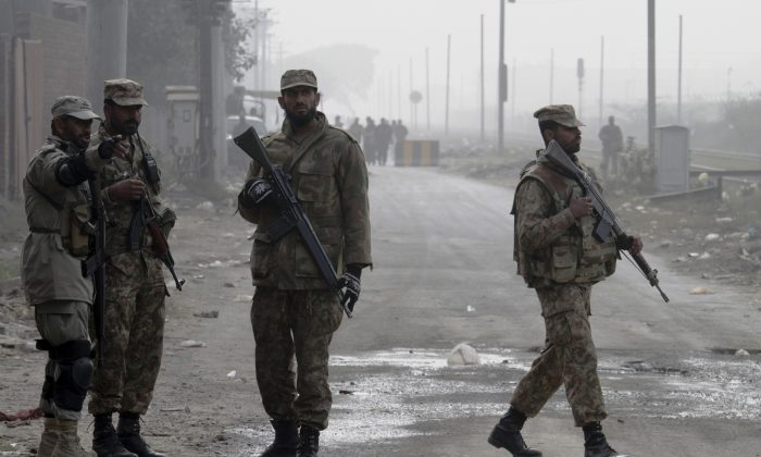 Pakistan army troops stand guard at a road on Dec. 20, 2014. (K.M. Chaudary/Photo via AP)