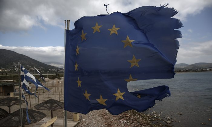 Ruined EU and Greek flags fly in tatters from a flag pole at a beach at Anavissos village, southwest of Athens, on Monday, March 16, 2015.  (AP/Yorgos Karahalis)